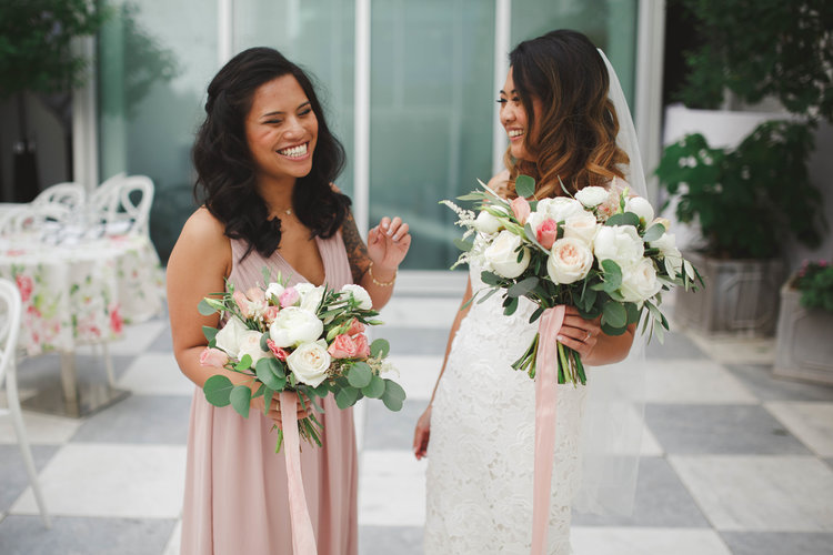 bride talking to bridesmaid in courtyard at quirk hotel richmond virginia
