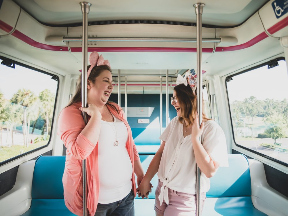 engaged couple holds hands on bus wearing pink mickey mouse ears