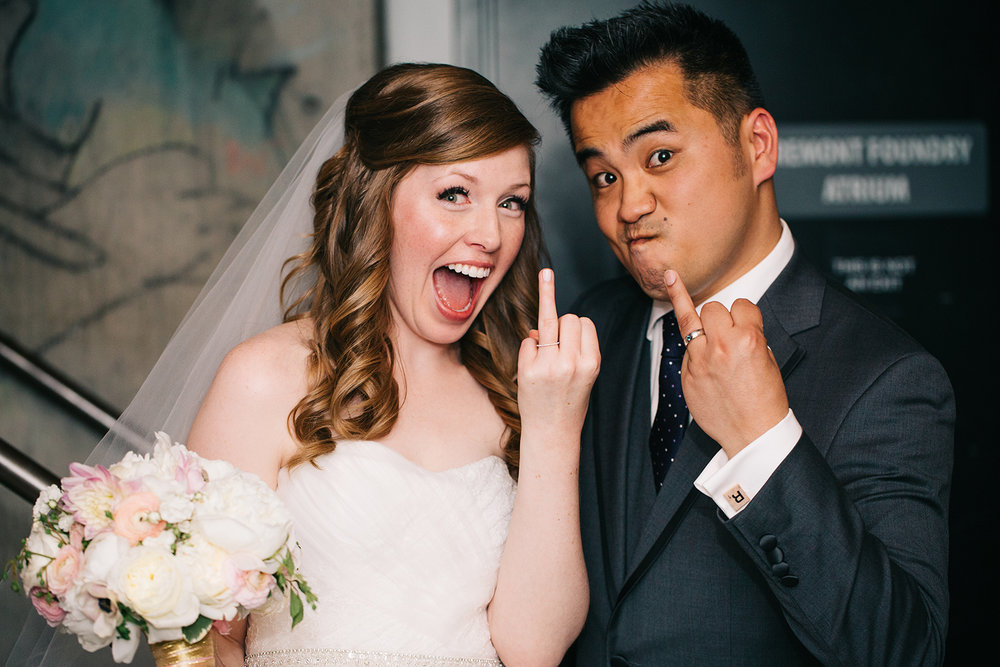 newlywed couple holding up ring fingers