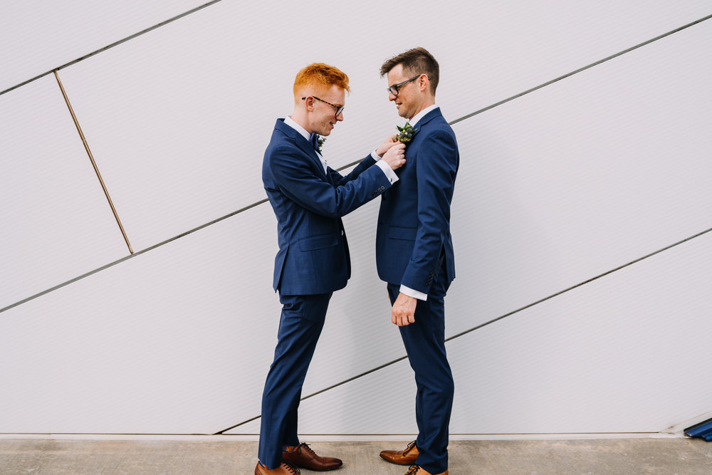 two grooms in blue suits one putting boutonniere on the other