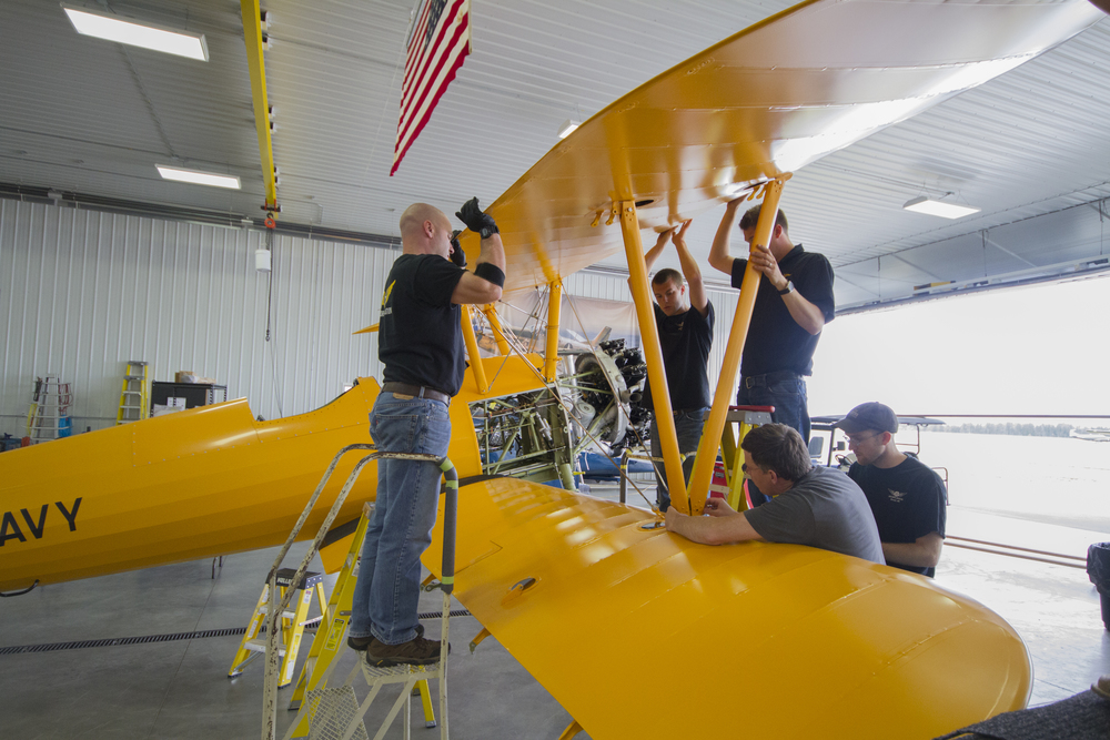 From left Brian, Simon, Erik, Mark (lower) and Sam work to rig the Stearman