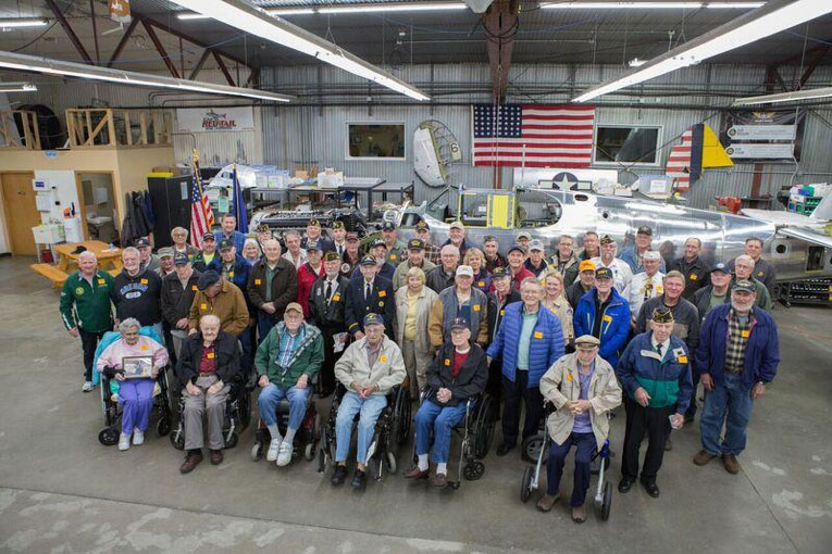 Veterans sitin front of Lope's Hope 3rd celebrating Veterans' Day at the AirCorps Aviation restoration shop.