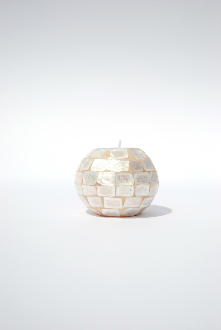 The round Glimmer candleholders in ivory shell are simple and elegant, complimenting any table design.