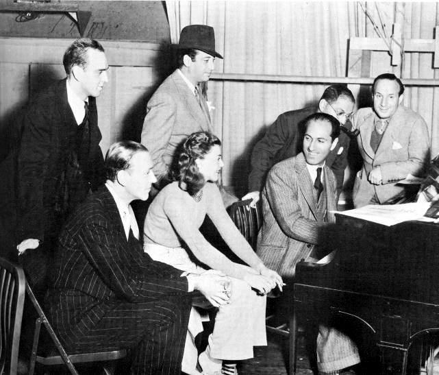 1936 年 《Shall We Dance》攝影場景。由左到右分別為:Hermes Pan(編舞)、Fred Astaire(佛雷)、Mark Sandrich(導演)、Ginger Rogers(金姐)、George Gershwin(作曲)、Ira Gershwin(填詞)、以及 Nat Shilkre(音樂總監)(via Songbook)