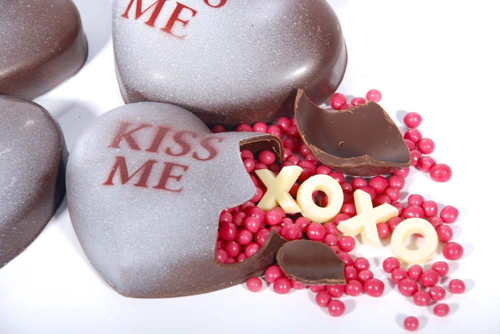"Heart-shaped chocolate ""rattle"" - break it open and ""hugs"" & ""kisses"" spill out, along with strawberry crisp pearls. Surprise!"