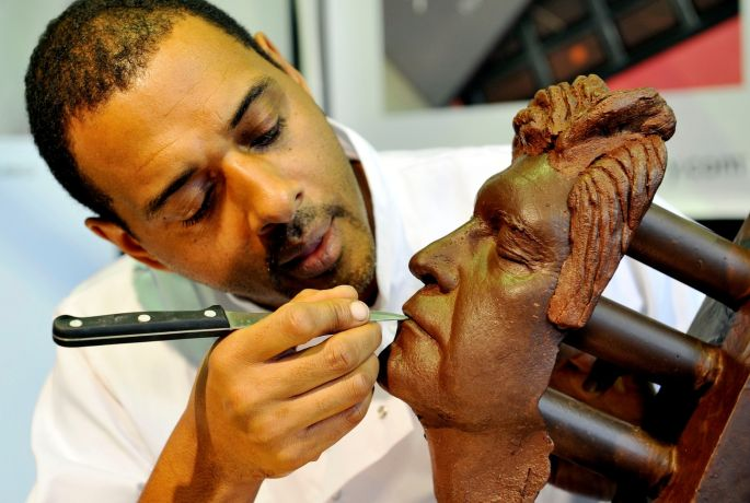 Chocolatier Paul Wayne Gregory works on a chocolate bust of Phillip Schofield during the Chocolate Show at Olympia's National Hall, London. Photograph: Nick Ansell/PA Wire