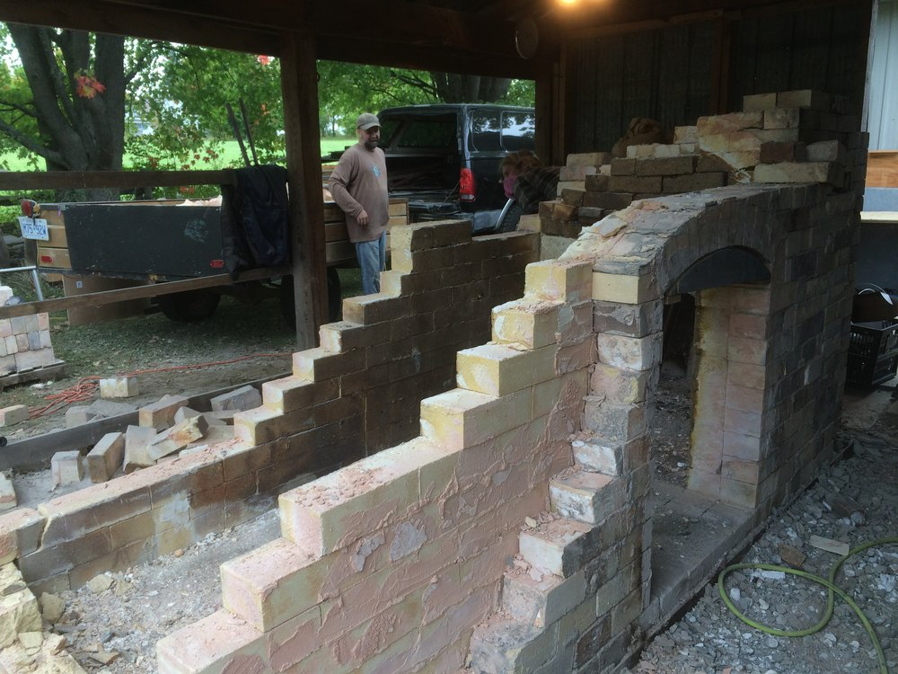 Step 5: Use any means possible to take the rest of the rear of the kiln down. For us this ranged from gentle tapping and chiselling, to me standing in the kiln whacking the back wall down with the sledgehammer. Some of the bricks were so stuck together that they were not salvageable.