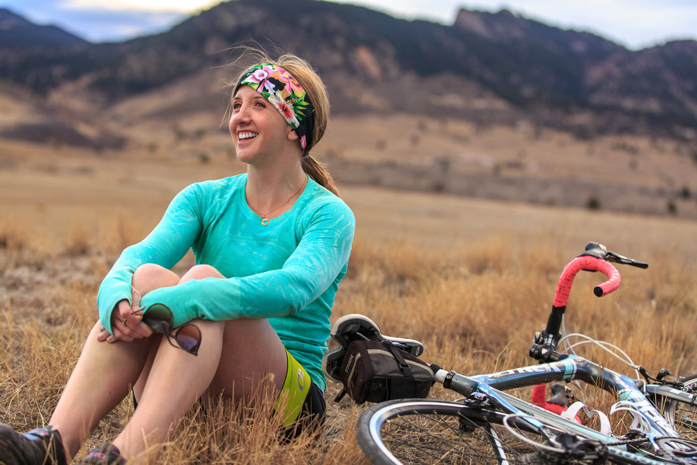 An athletic woman in Colorado sits near her bike after a long bicycle ride to soak in the sun and enjoy the scenery of the Rocky Mountains.
