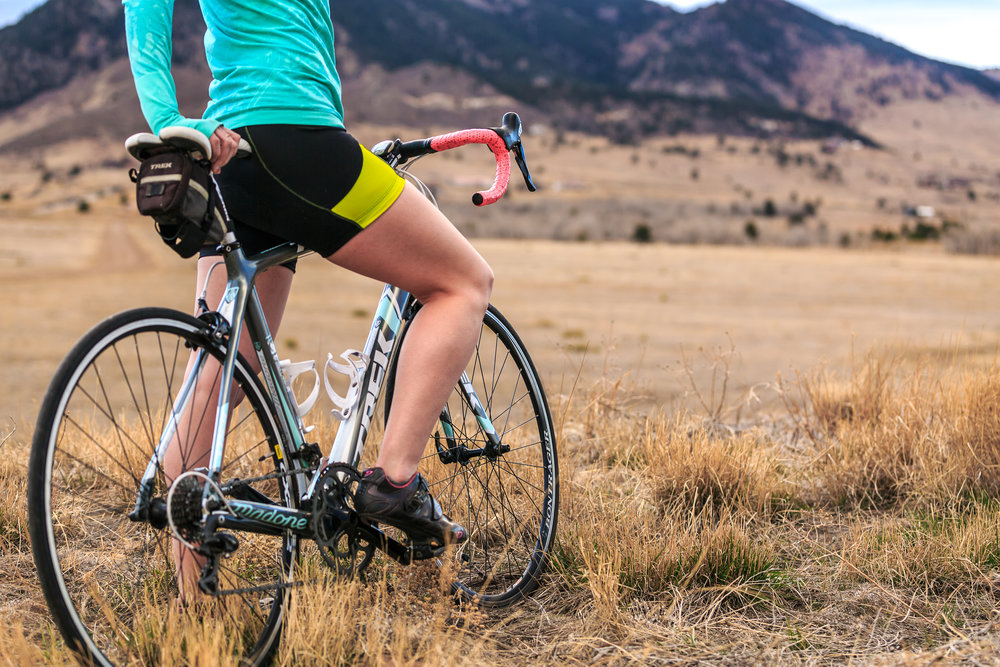 An athletic female bike rider in Colorado adjusts her bike as she trains for the Courage Classic bicycle tour in the Rocky Mountains.