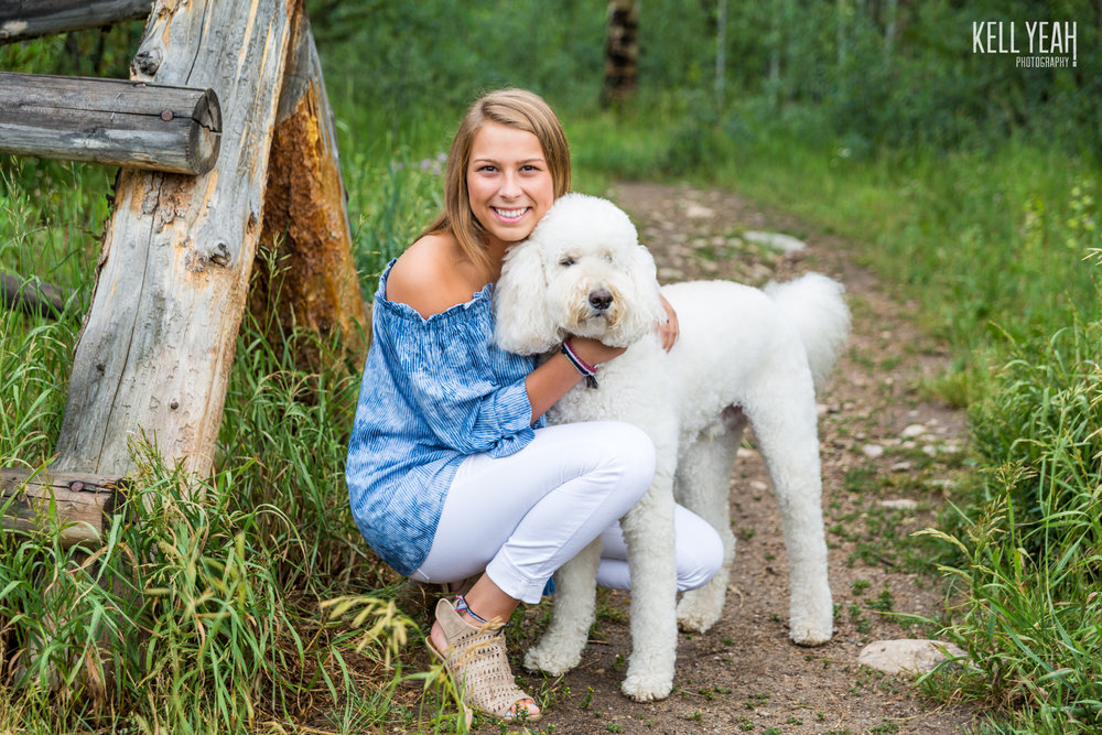 A beautiful young lady hugs her goldendoodle dog during a family photo shoot in the mountains near Lake Granby, Colorado.