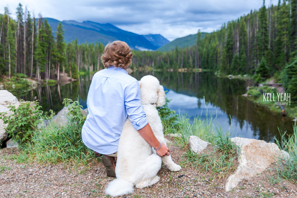 A boy and his dog sit in front of a lake in the mountains of Colorado for a photo session with KellYeah Photography.