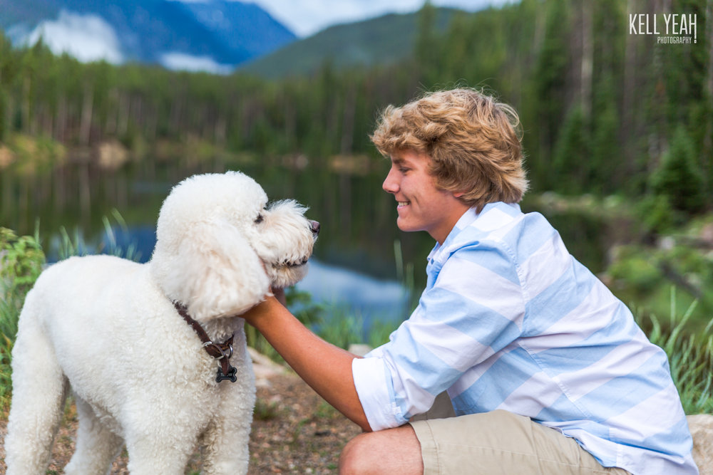A high school boy and his goldendoodle dog take a photo together in the Colorado mountains with KellYeah Photography.
