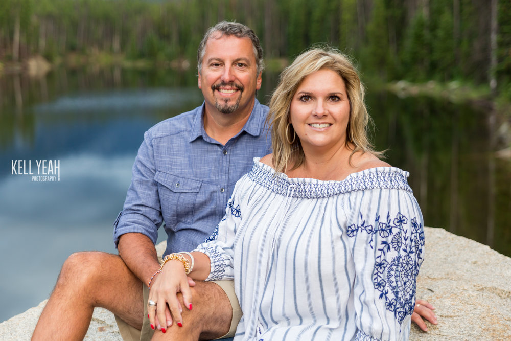 A husband and wife sit on a rock near Lake Granby in the Colorado Rocky Mountains during a family photo shoot with KellYeah Photography.