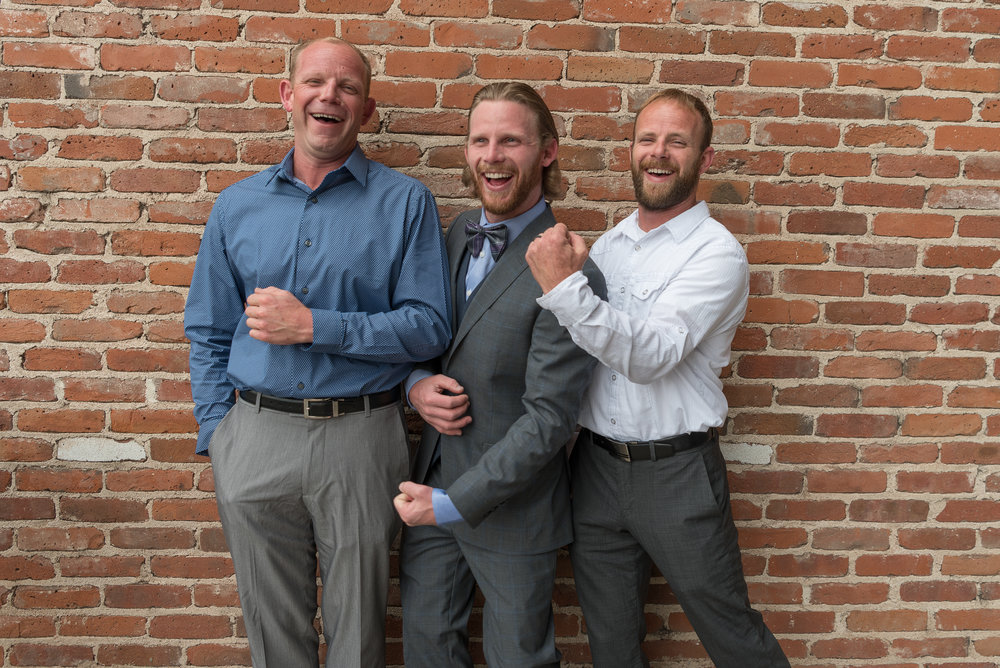 Three brothers joke and banter during a family photo shoot before one man's wedding at Mile High Station in Denver, Colorado.