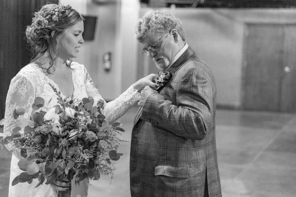 A bride helps her father with his boutonniere before they walk down the aisle on her wedding day.