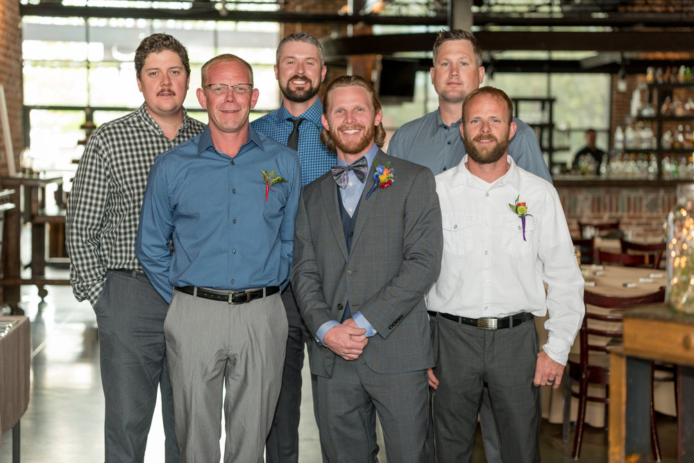 A groom and his groomsmen gather before the wedding wearing suits and ties and smiling.