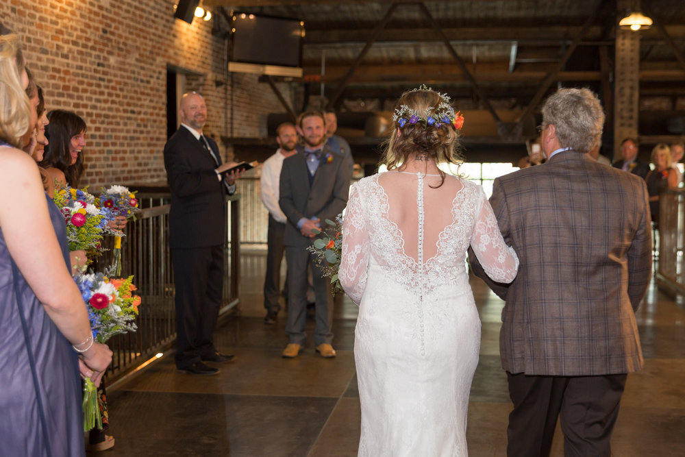Bride walks down the aisle toward her groom at Mile High Station in Denver, Colorado. She wears a lacy bridal gown and he wears a lavender tuxedo with a bowtie.