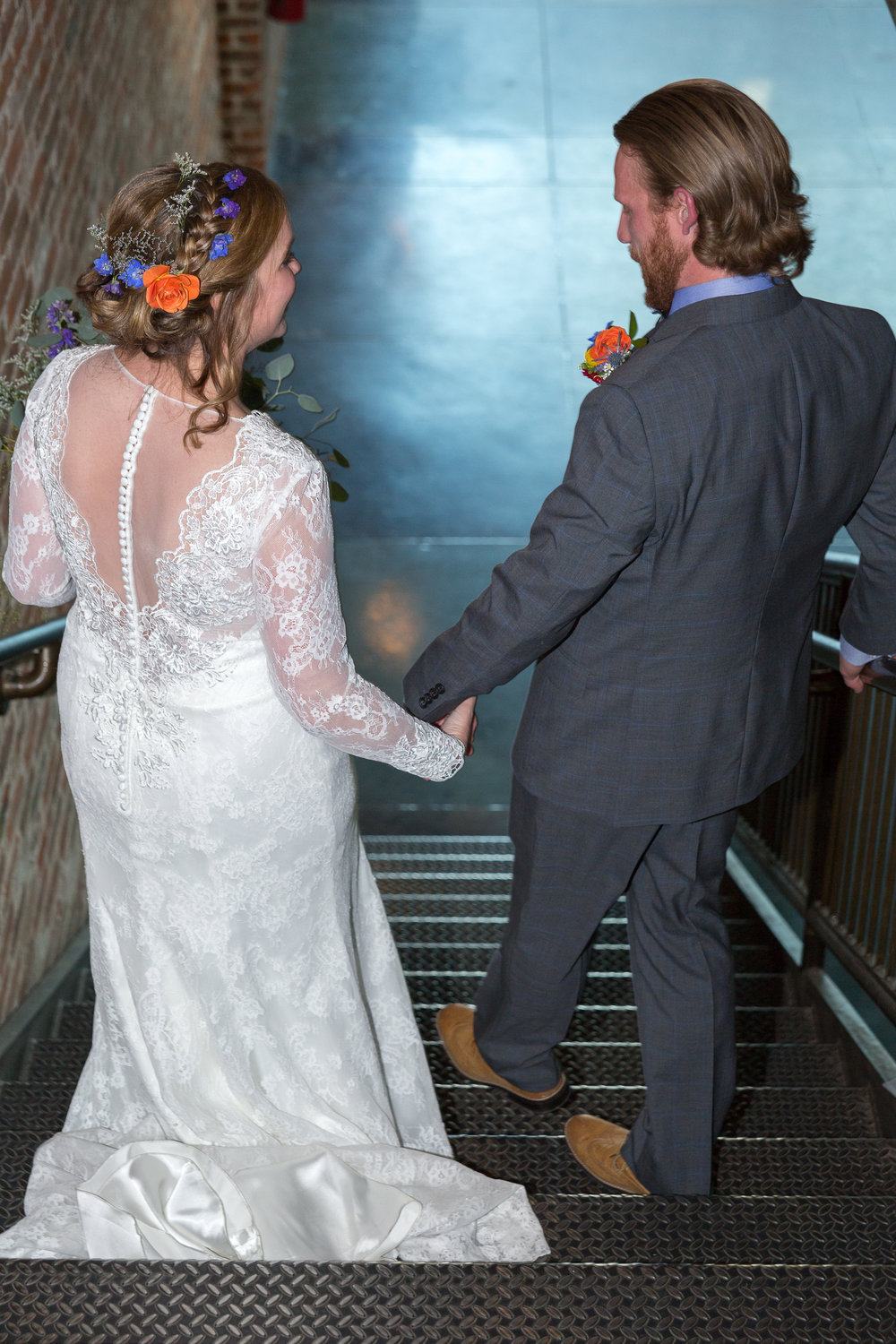 Bride and groom walk down the stairs after their wedding ceremony.