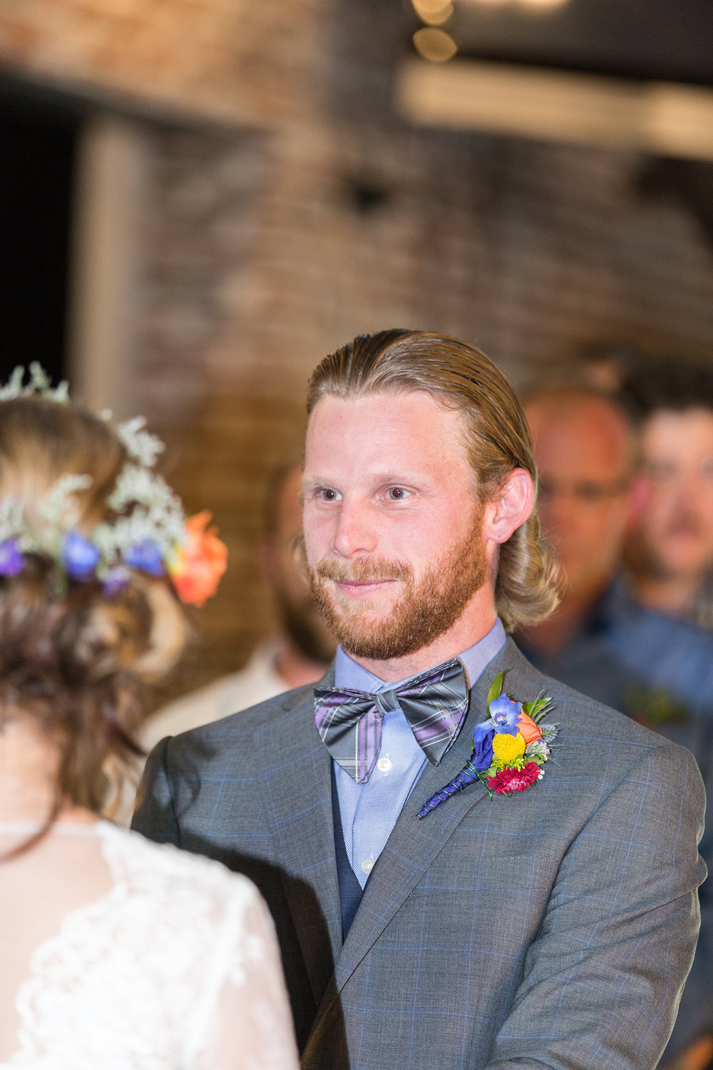 Blond-haired groom gazes at his bride during their wedding ceremony in June in Colorado.