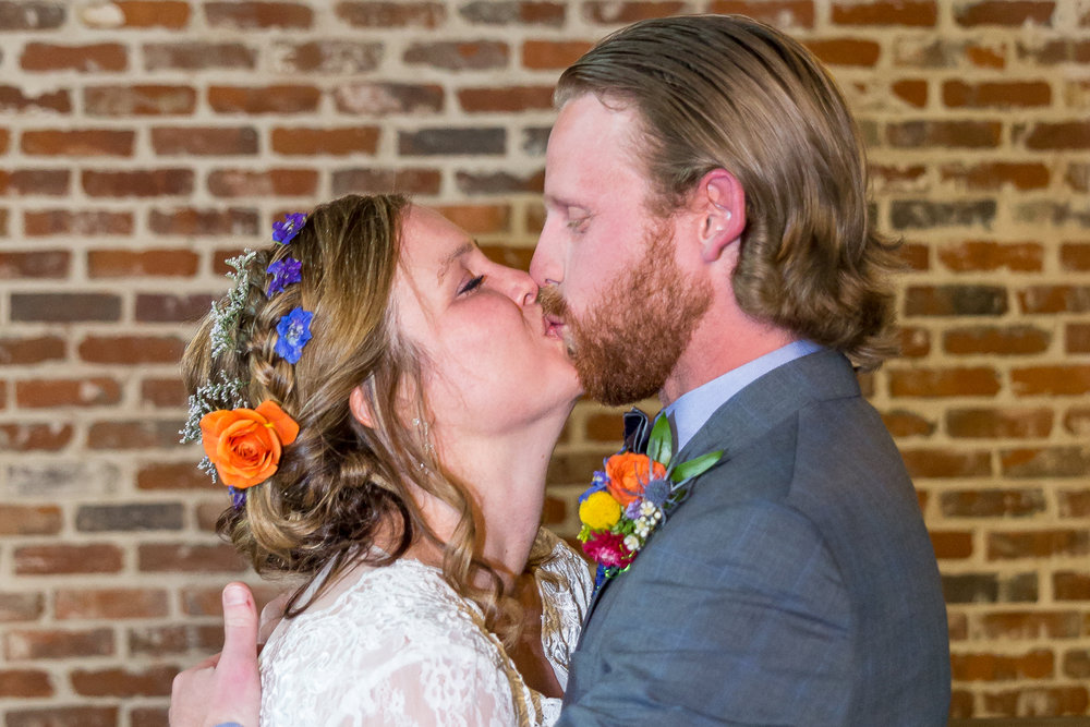 Bride and groom first kiss wearing flower crown with roses and wildflowers