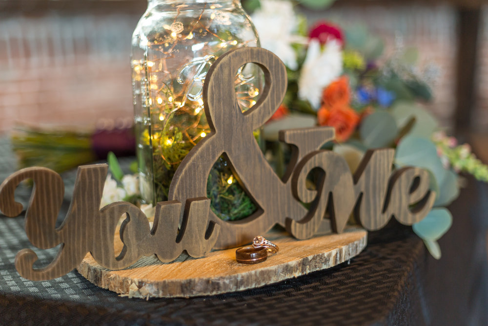 Wedding rings stacked on a wooden board and next to a decorative piece made of wood that says You & Me
