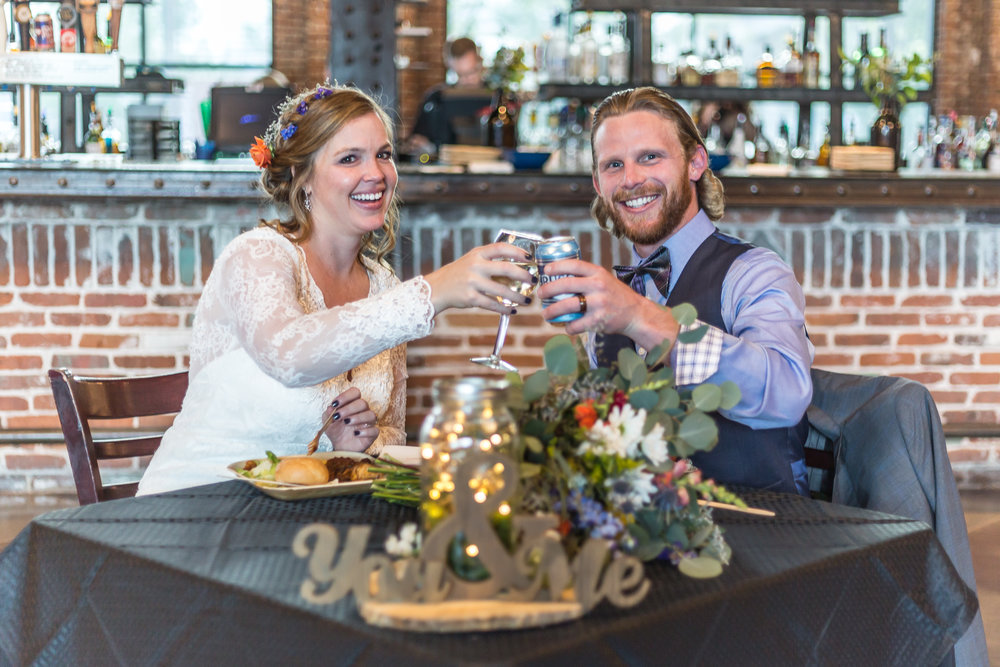 Bride and groom at Mile High Station in Denver, Colorado toast each other during their wedding reception