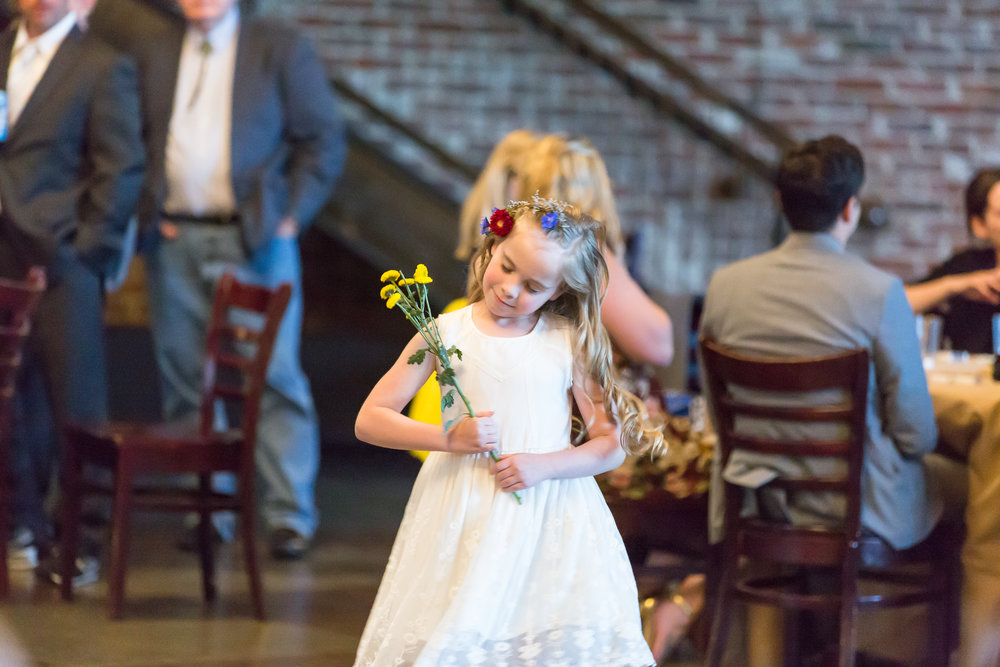 Flower girl dances with wildflowers and a flower crown in her hair at a wedding in Denver, Colorado