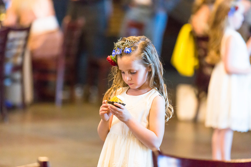 Flower girl wearing cream white dress and crown of wildflowers with a braid in her hair eats a cupcake during a wedding reception in Denver, Colorado