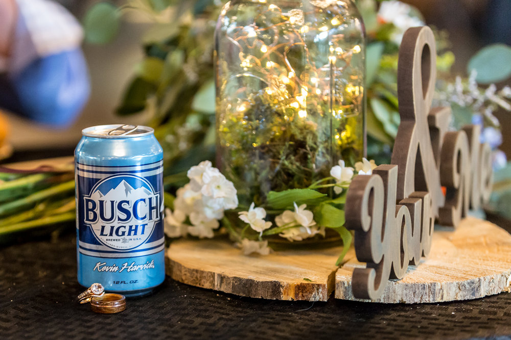 A can of Busch beer placed next to bride and groom's wedding rings at their reception in Denver, Colorado