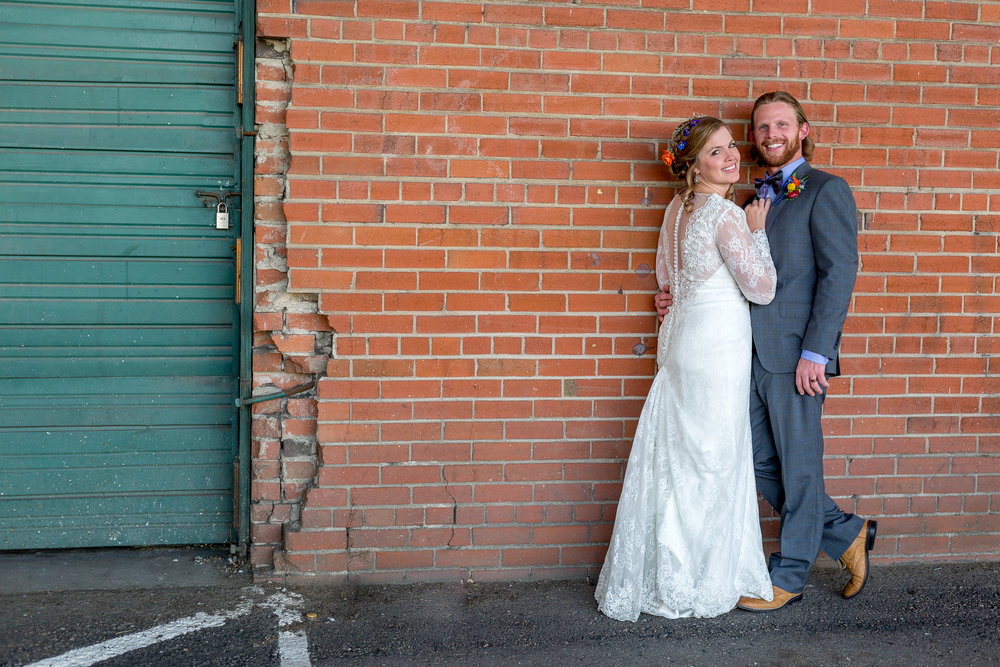Bride wearing long lace bridal gown poses with her groom wearing tan loafers and a dark blue tuxedo.