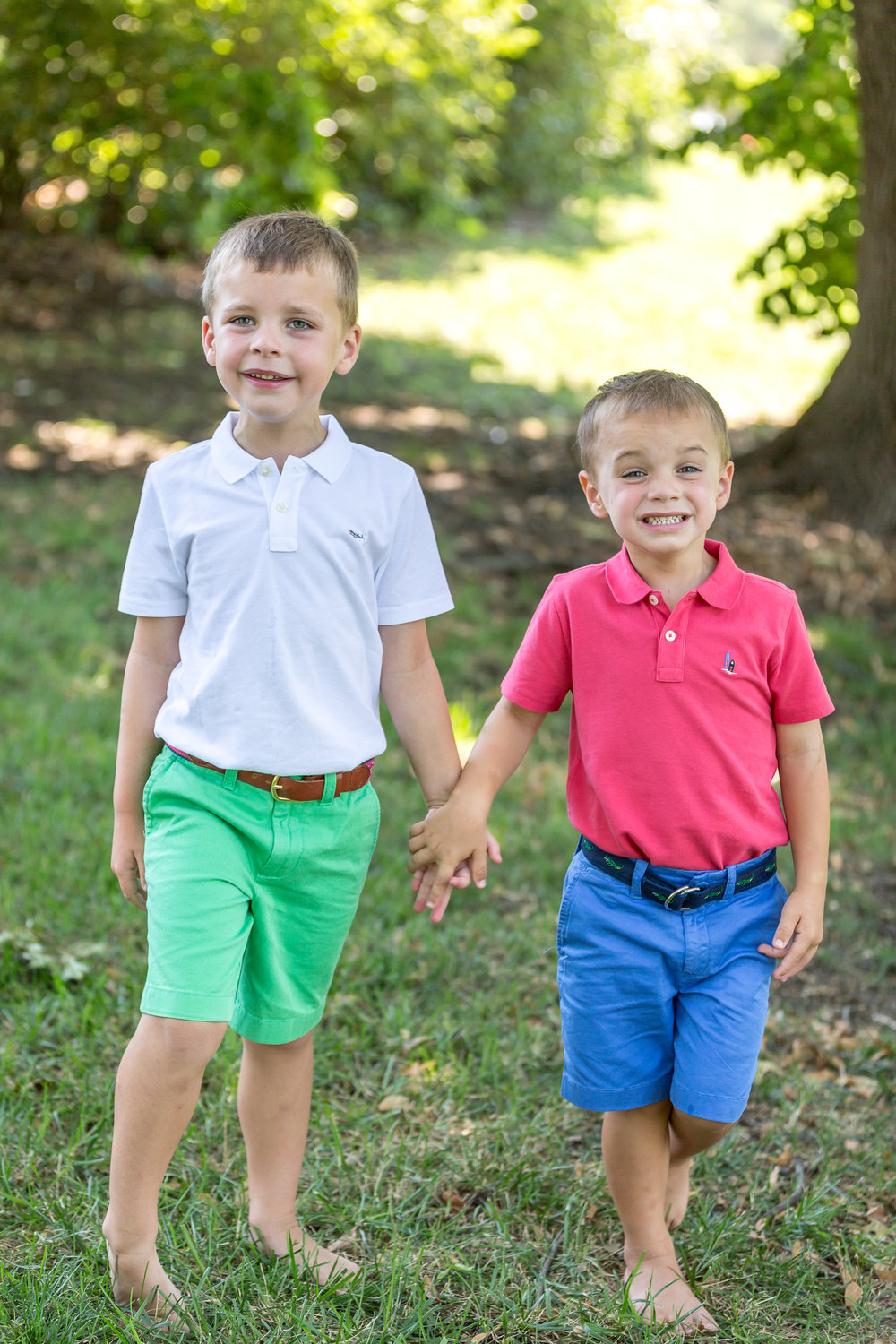 Brothers in Kansas City holding hands at Loose Park during family photo shoot with big smiles
