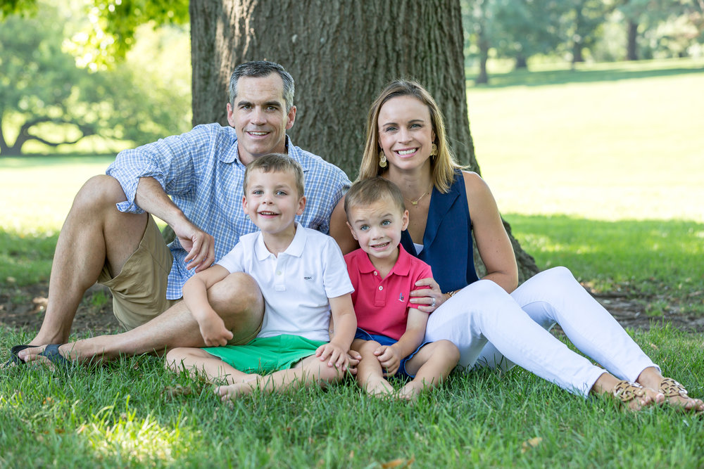 A Kansas City family with two young boys sits in grass relaxing during photo shoot
