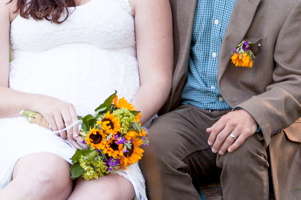 colorado bride and groom hands resting with sunflowers in elopement at rocky mountain national park
