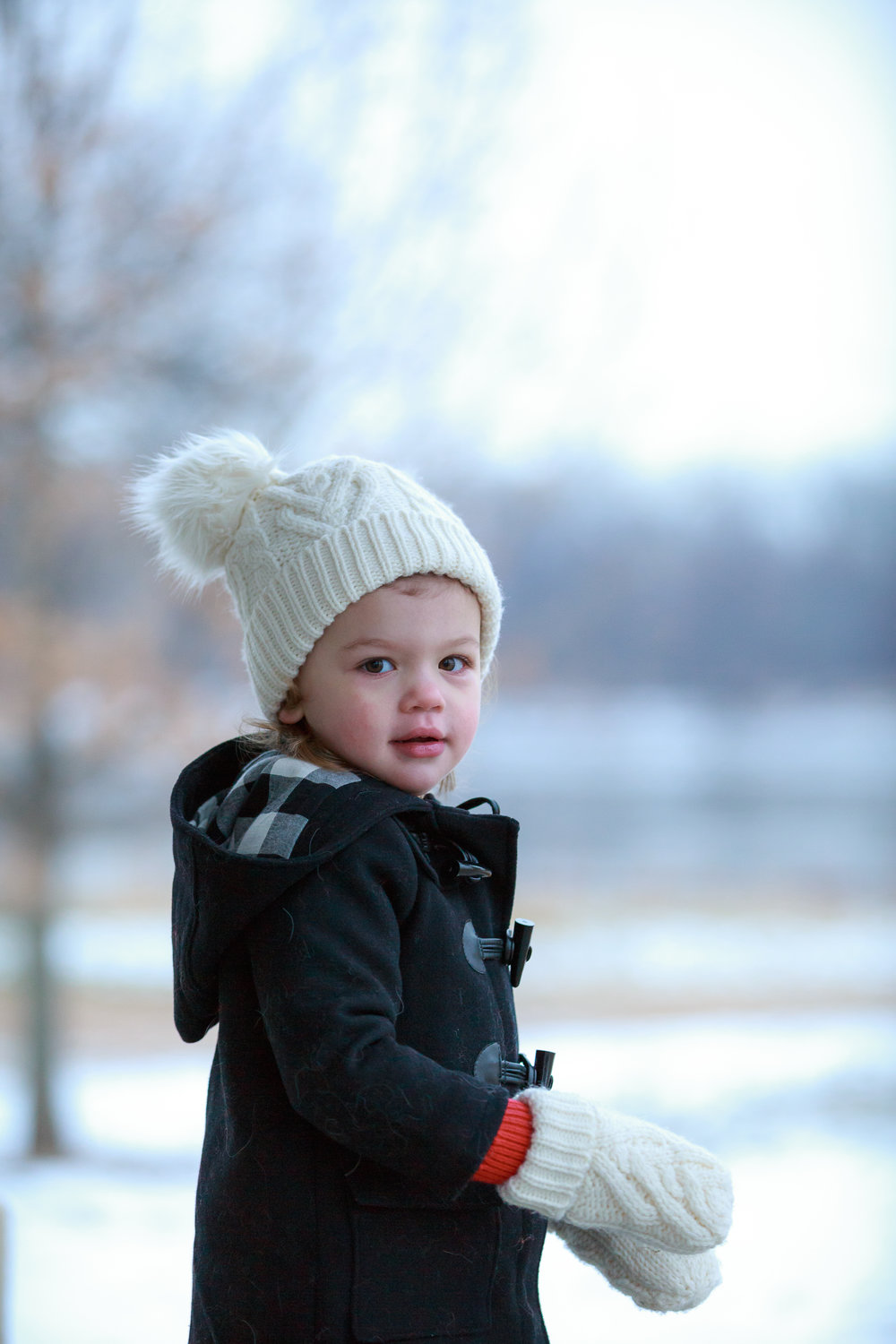 Young girl wearing knit hat and peacoat and mittens enjoying a winter afternoon in St. Charles, Missouri near the river.