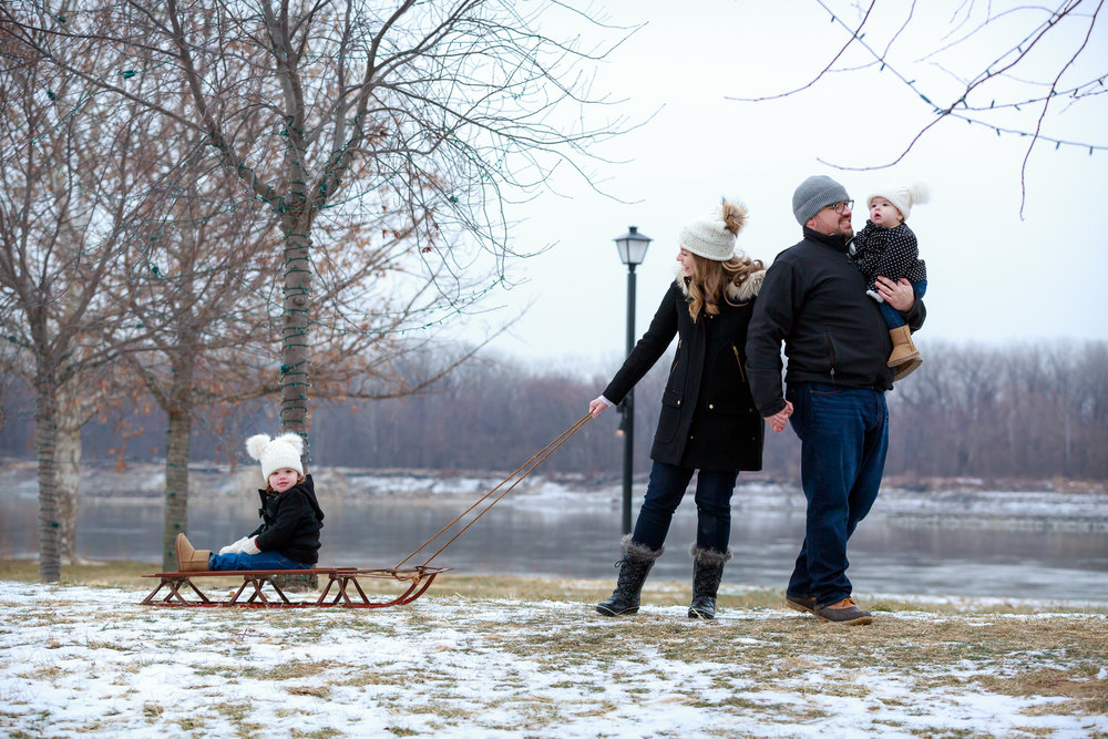 Young family with a toddler and a baby girl walk while pulling a sled along the riverbank in St. Charles, Missouri. The girl wears a knit hat and Ugg boots with her peacoat and mittens.