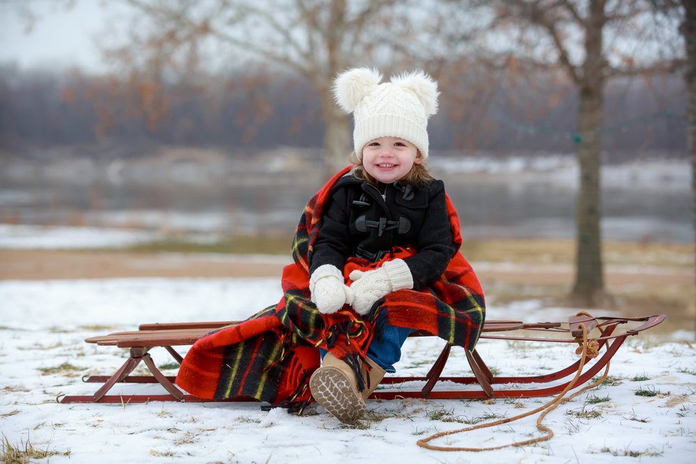 A young girl smiles while wearing a knit hat, mittens, and a peacoat sits on a wooden sled under a red flannel blanket on a cold winter day.