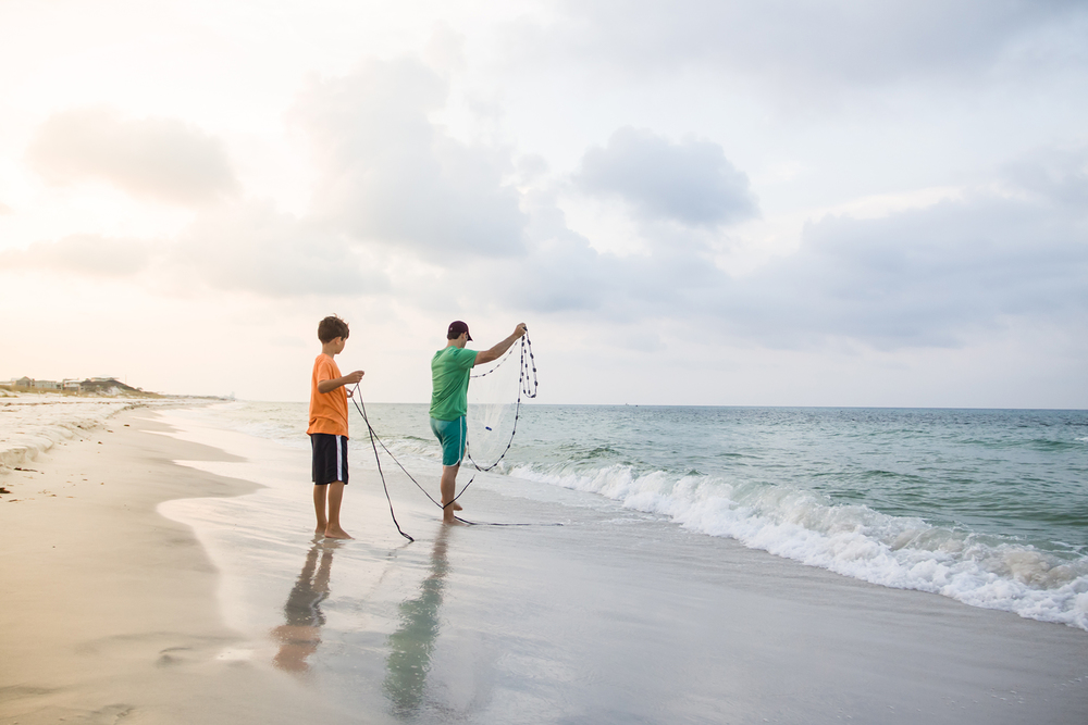 Father and son wielding a bait net.