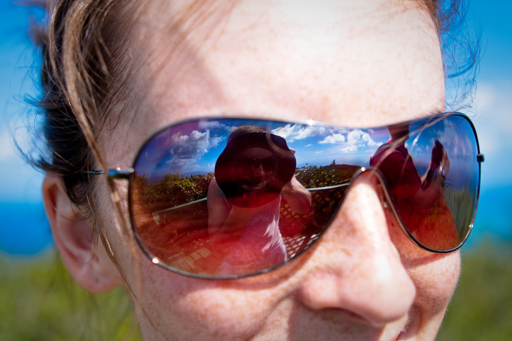 Clouds and blue sky reflection in sunglasses of a female adventurer.