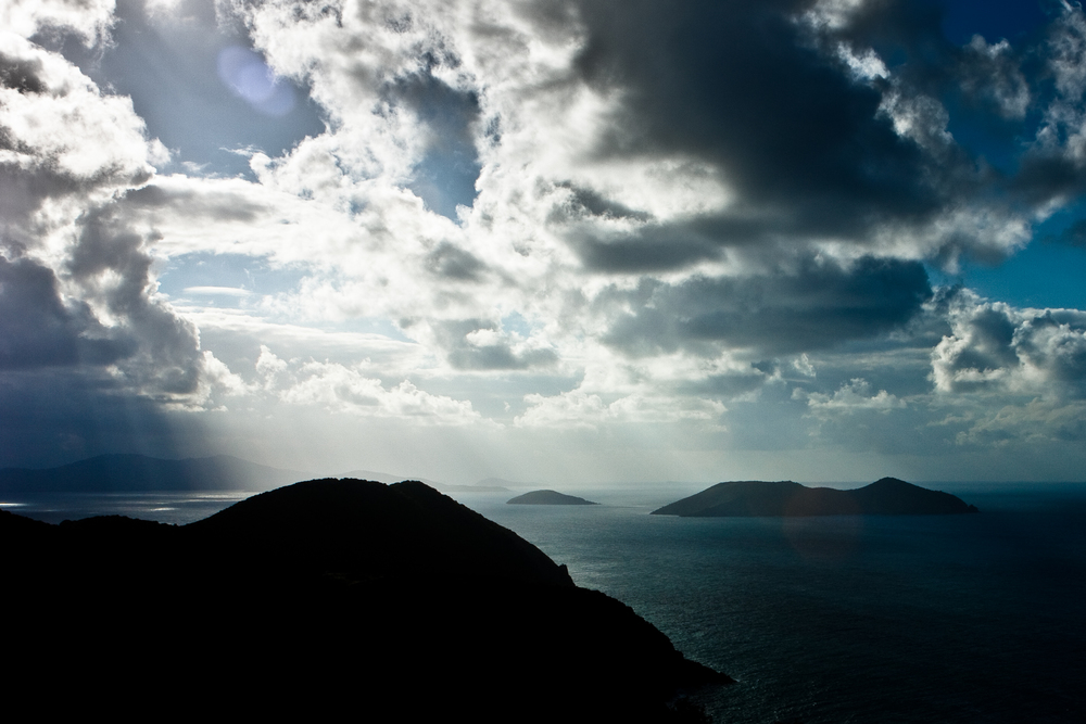 Sunlight rays stream through storm clouds over a chain of islands and silhouettes.