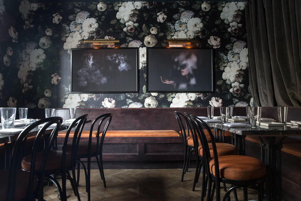 """RIOJA"" PRIVATE DINING ROOM    Rioja is our largest private dining room with custom built wood and leather seating, bold wallpaper, antique mantel, and black marble table tops.    Seats up to 32 people."