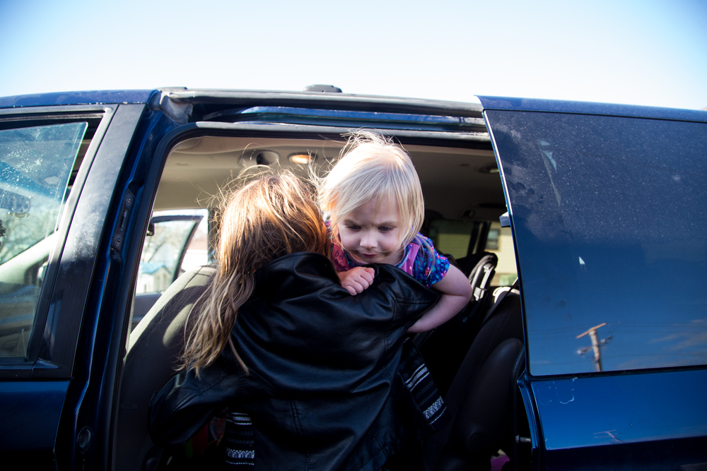 Lynae loads her baby sister Ariella into the family's minivan before leaving the Family Promise day Center for the church they will be sleeping in for the night.