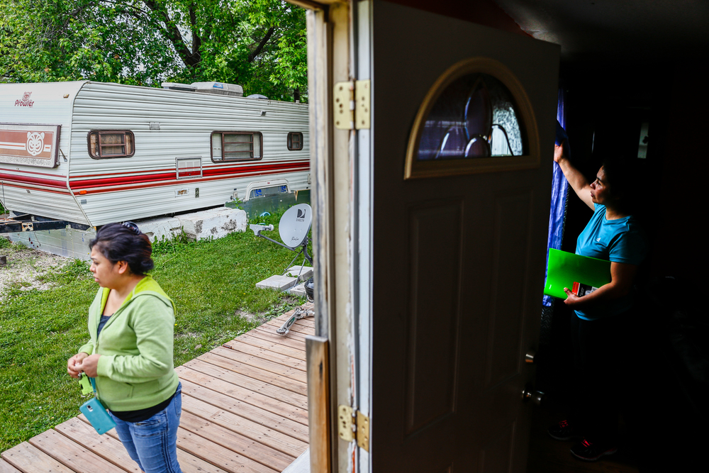 Antonia Alvarez looks out from a neighbors renovated trailer in Lowry Grove mobile home park.