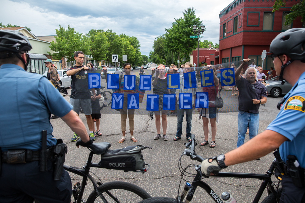 "Protesters hold a sign reading ""blue lies matter"" in front of a group of bicylcle officers on a march from the governor's mansion to JJ Hill Montessorri in St. Paul, Minnesota."