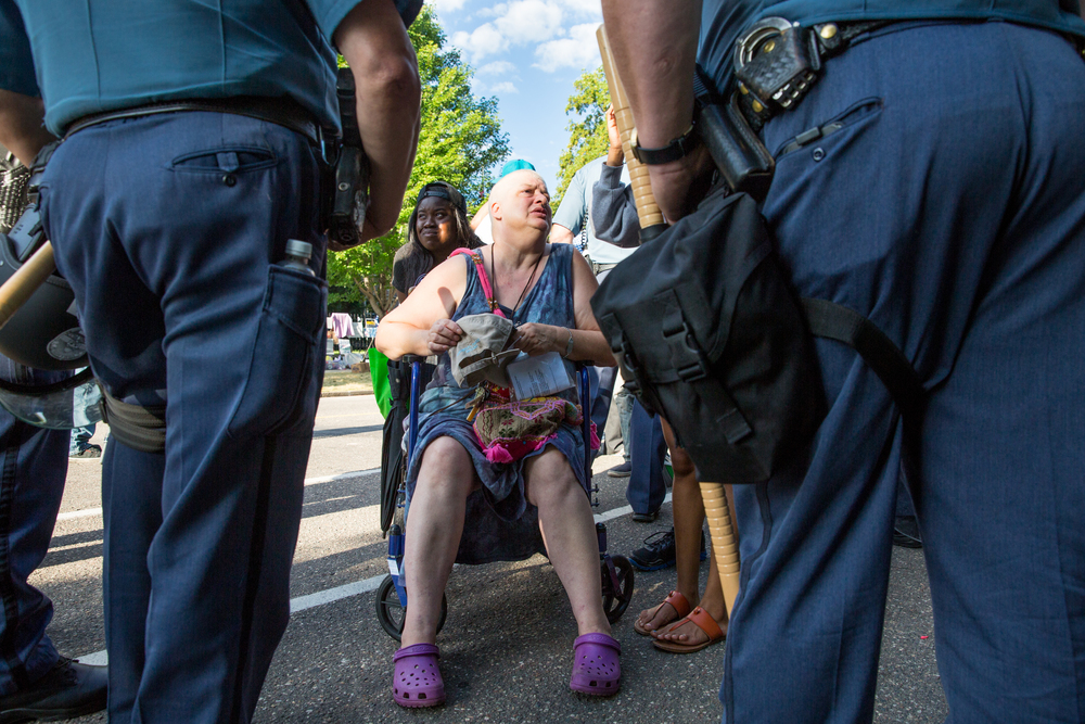 A protester confronts speaks with the police after being asked to leave the encampment outside of the Governor's Mansion in St. Paul, Minnesota.