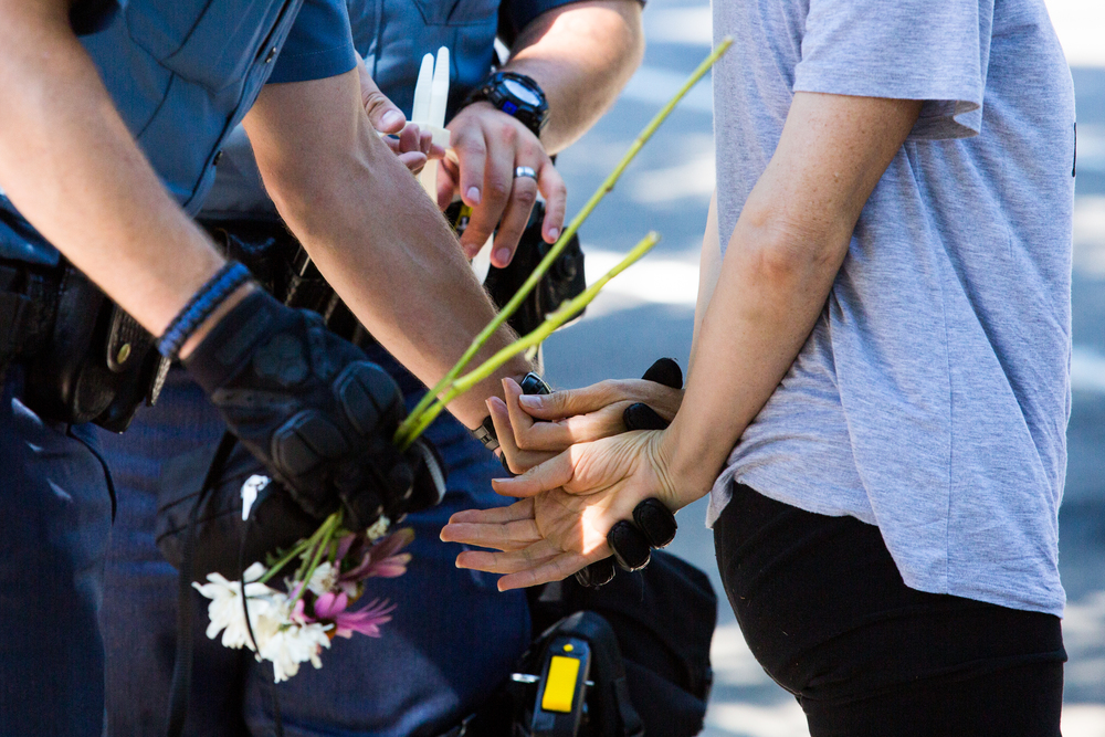 Police remove the flowers from a protesters hand before putting her in handcuffs.