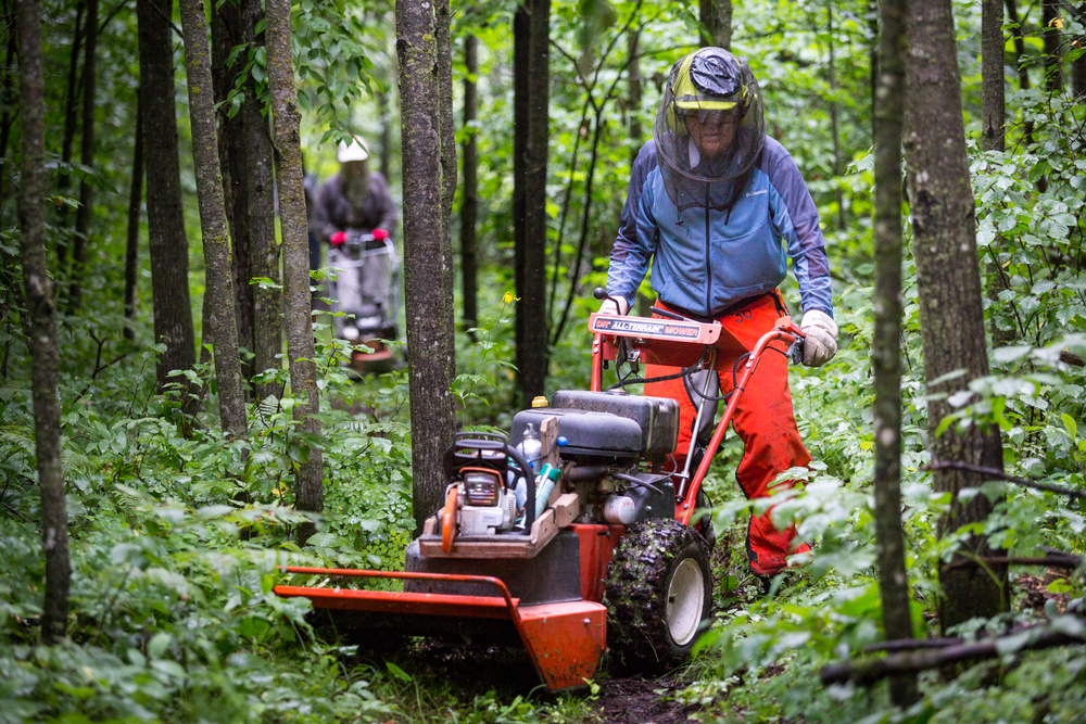 Jim Rakness pushes an all terrain lawn mower down the North Country Scenic Trail.