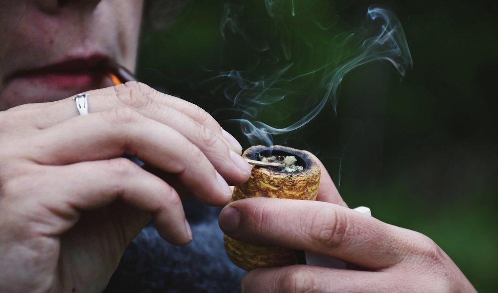Hand lighting corncob pipe smoking herbs rainy background smoke