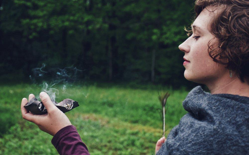 Amanda Midkiff of Locust Light farm smudging burning herbs in sacred ritual sacred ceremony