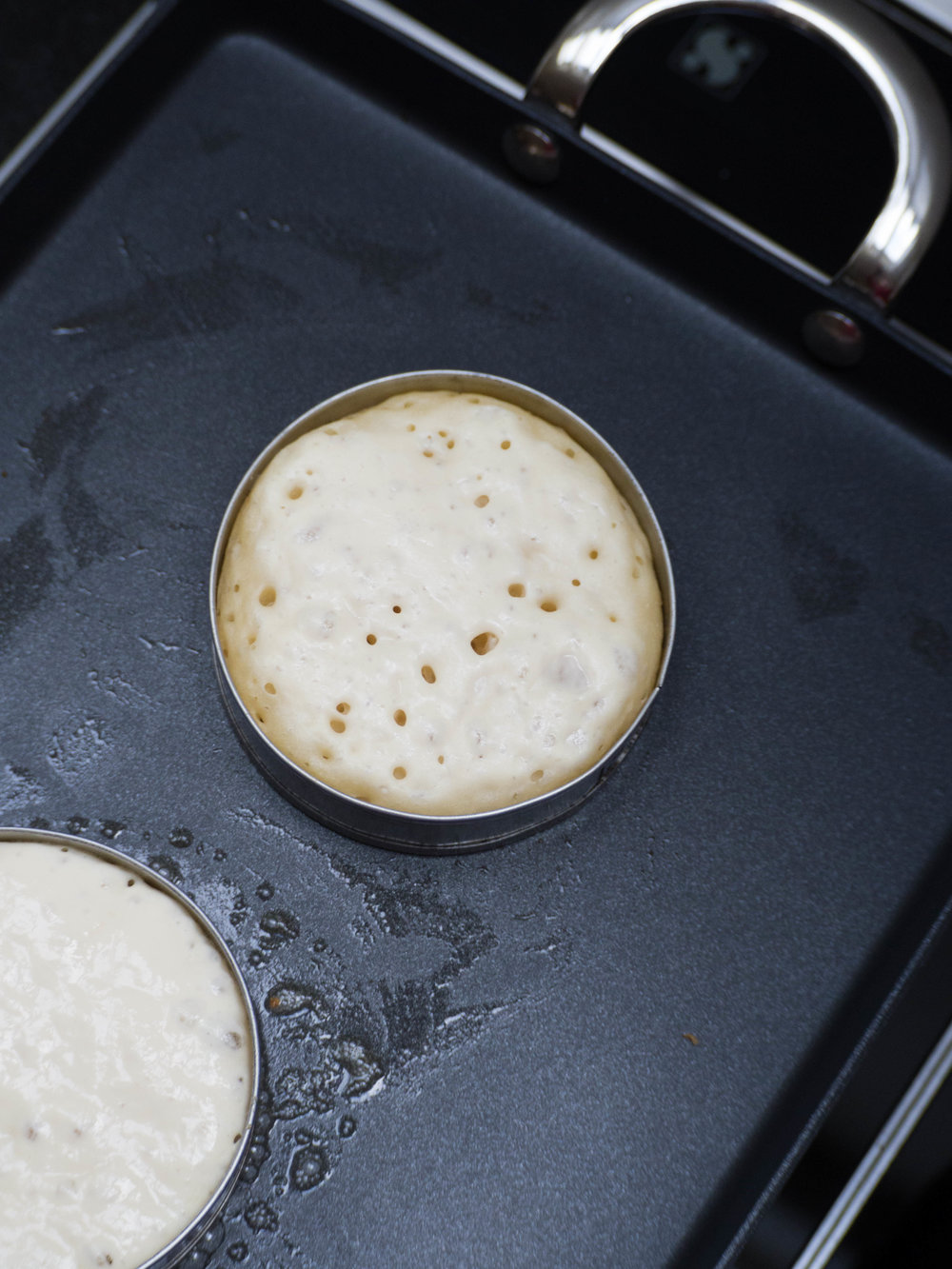 Cook crumpets on low heat in a crumpet ring until bubbles then holes appear, then flip