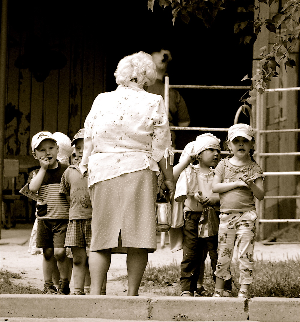 The children wait eagerly for us to arrive and play with them as their caretaker crossly tries to organize them.